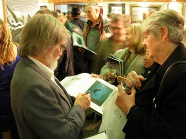 Tofino artist Mark Hobson signing a book at the Nanaimo opening. Mark instigated and coordinated the Art For an Oil-Free Coast project.