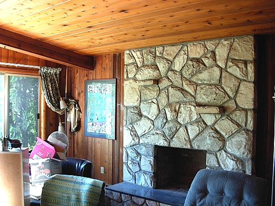 Living Room has a floor-to-ceiling split lime fireplace (wood-burning) with polished marble heart, vaulted ceiling, panoramic window and knotty pine walls and ceiling