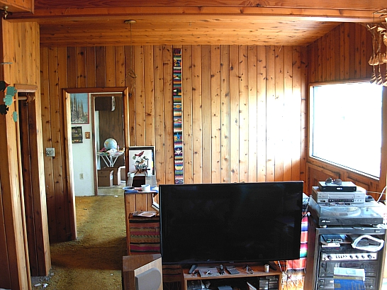 The knotty pine of the living room continues into the foyer